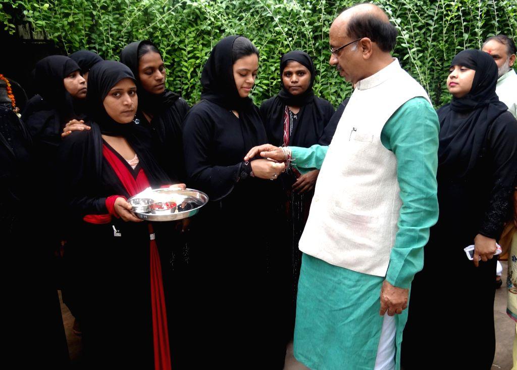 Muslim women tie rakhi on the wrist of BJP leader and Rajya Sabha member Vijay Goel at his residence in New Delhi on Aug 10, 2014.