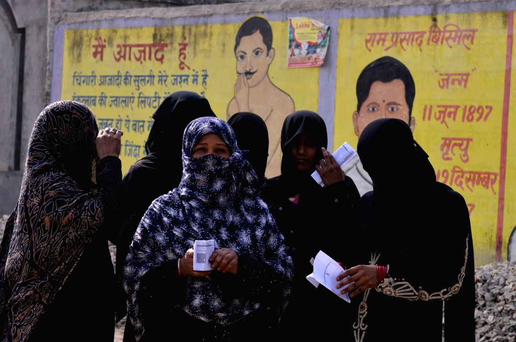 Muslim women wait outside a polling booth to caste their vote for the 2019 Lok Sabha elections in Navala village UttarPradesh Muzaffarnagar district, on April 11, 2019.