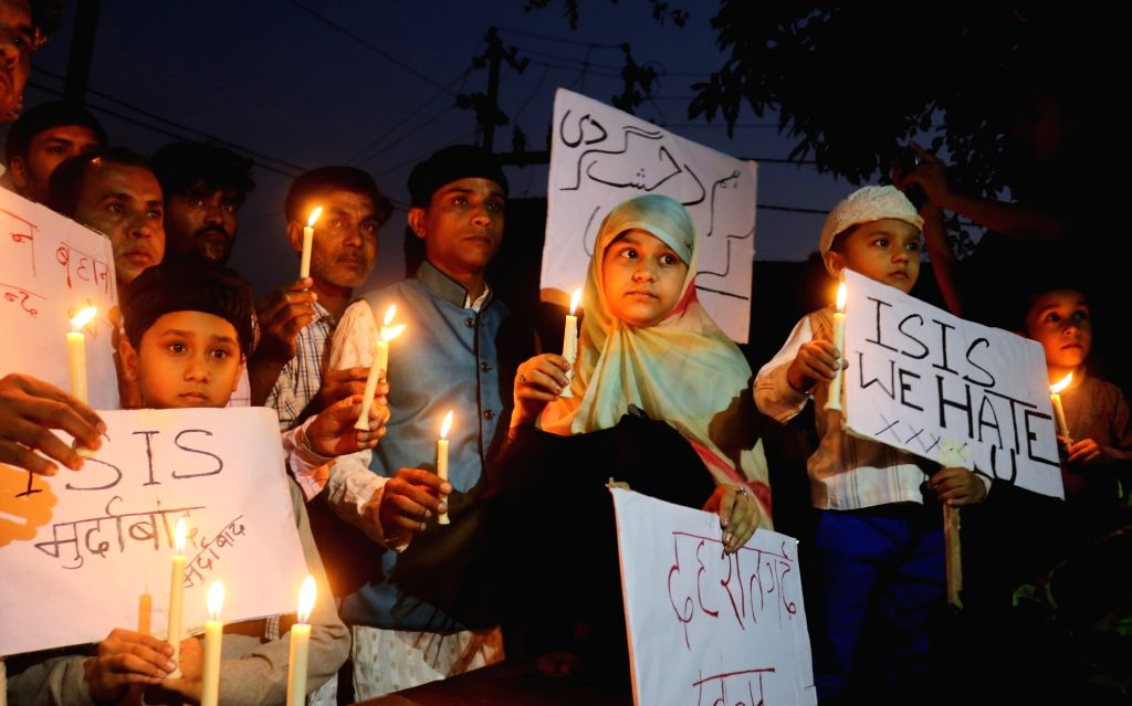 Muslims hold candles to mourn the victims of a series of attacks in Paris; in Bhopal on Nov 15, 2015.