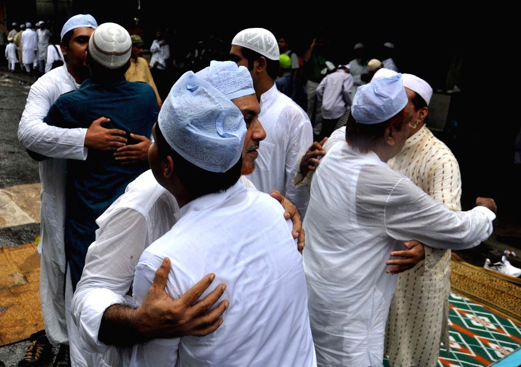 Muslims hug after Eid-ul-Fitr prayers at the Nakhoda Mosque in Kolkata on July 29, 2014.