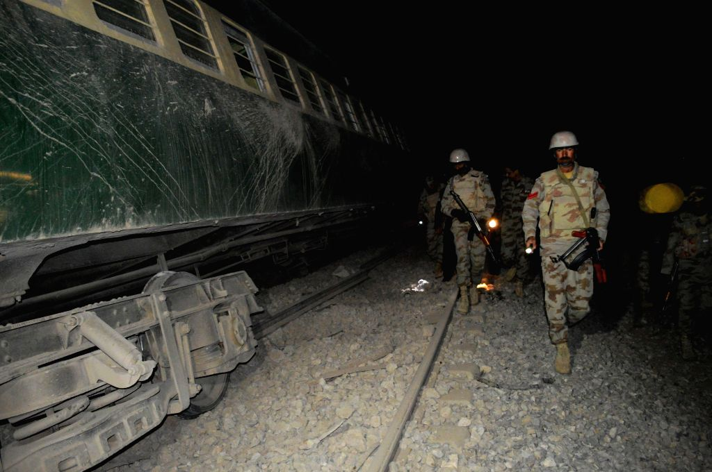 Mustang (Pakistan): Pakistani soldiers inspect the train at the blast site in southwest Pakistan's Mustang on Nov. 20, 2014. At least 12 people were injured when a passenger train derailed after a ...
