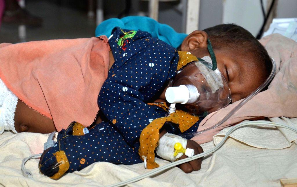 Muzaffarpur: A child with Acute Encephalitis Syndrome (AES) symptoms being treated at hospital in Muzaffarpur, Bihar on June 19, 2019. (Photo: IANS)