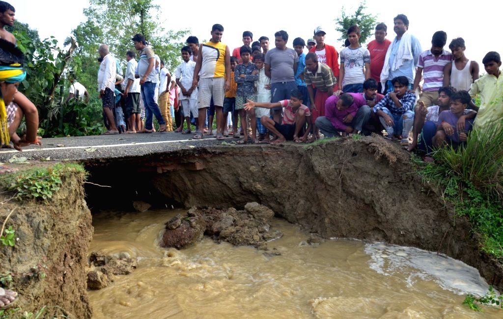 Muzaffarpur: Flood water washes land underneath a road in Katra block of Muzaffarpur on July 15, 2019. (Photo: IANS)