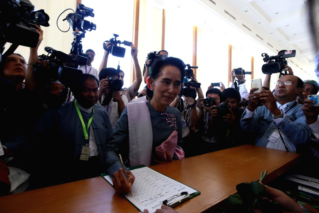 Myanmar's National League for Democracy (NLD) Chairperson Aung San Suu Kyi (C) signs on registration forms to attend the 13th regular session of the House of ...