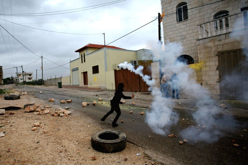 A Palestinian protester hurls back a tear-gas canister shot by Israeli soldiers during a protest against the expanding of Jewish settlements in Kufr Qadoom Village near the West Bank city of .