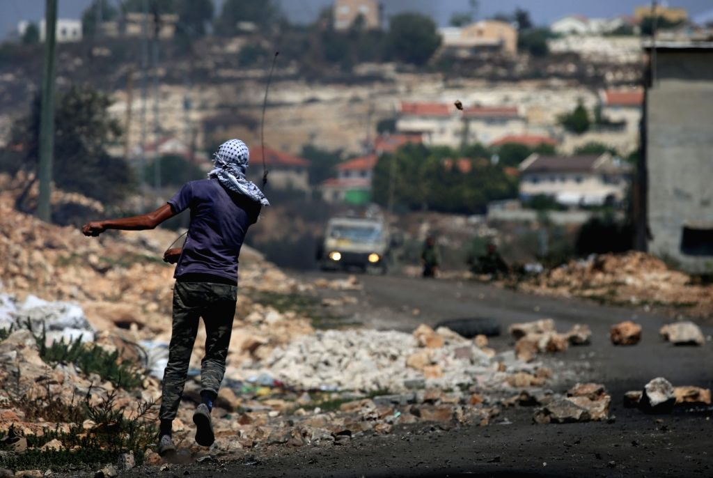 NABLUS, Aug. 11, 2017 - A Palestinian protester hurls a stone at Israeli soldiers during clashes after a protest against the expanding of Jewish settlements in Kufr Qadoom village near the West Bank ...