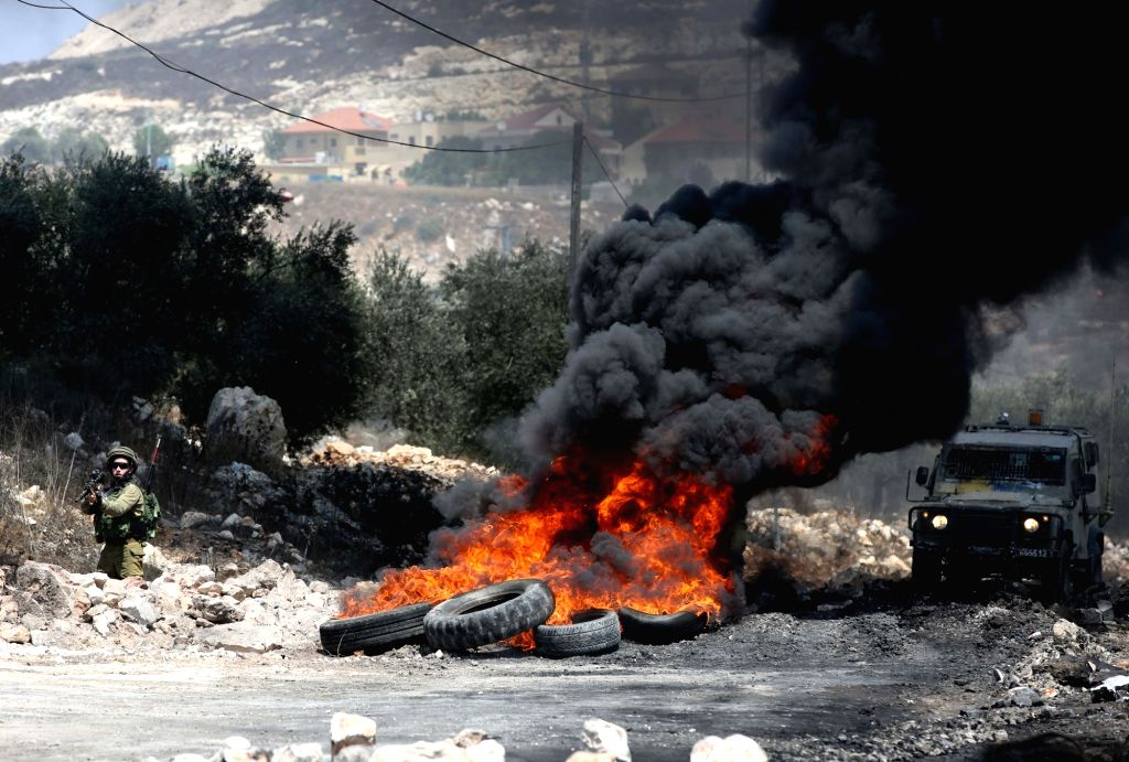NABLUS, Aug. 11, 2017 - An Israeli soldier confronts Palestinian protesters during clashes after a protest against the expanding of Jewish settlements in Kufr Qadoom village near the West Bank city ...