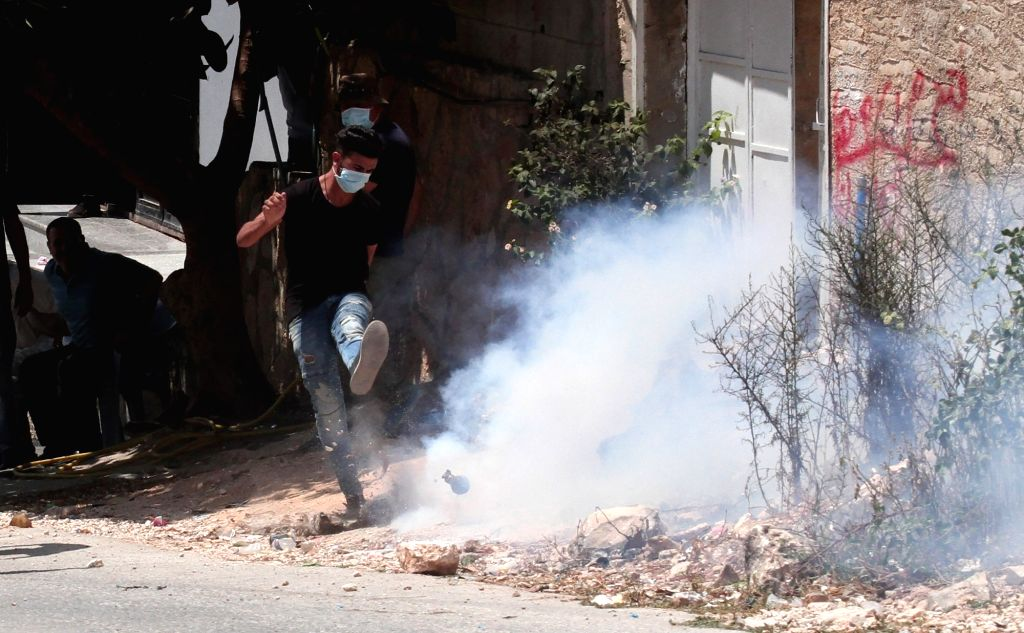 NABLUS, Aug. 11, 2018 - A Palestinian protester kicks back a tear gas canister at Israeli soldiers during clashes after a protest against the expanding of Jewish settlements in Kufr Qadoom village ...