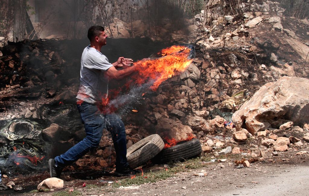NABLUS, Aug. 2, 2019 - A Palestinian protester burns tires during clashes with Israeli soldiers after a protest against the expansion of Jewish settlements in Kufr Qadoom village near the West Bank ...