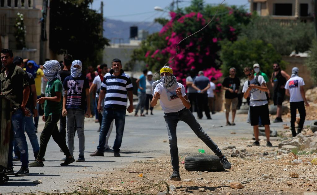 NABLUS, Aug. 9, 2019 - A Palestinian protester uses a slingshot to hurl stones at Israeli soldiers during clashes following a protest against the expansion of Jewish settlements in Kufr Qadoom ...