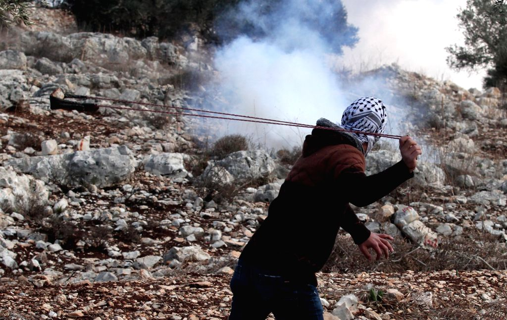 NABLUS, Dec. 6, 2019 - A Palestinian man hurls stones at Israeli soldiers during clashes after a protest against the expanding of Jewish settlements in Kufr Qadoom village near the West Bank city of ...