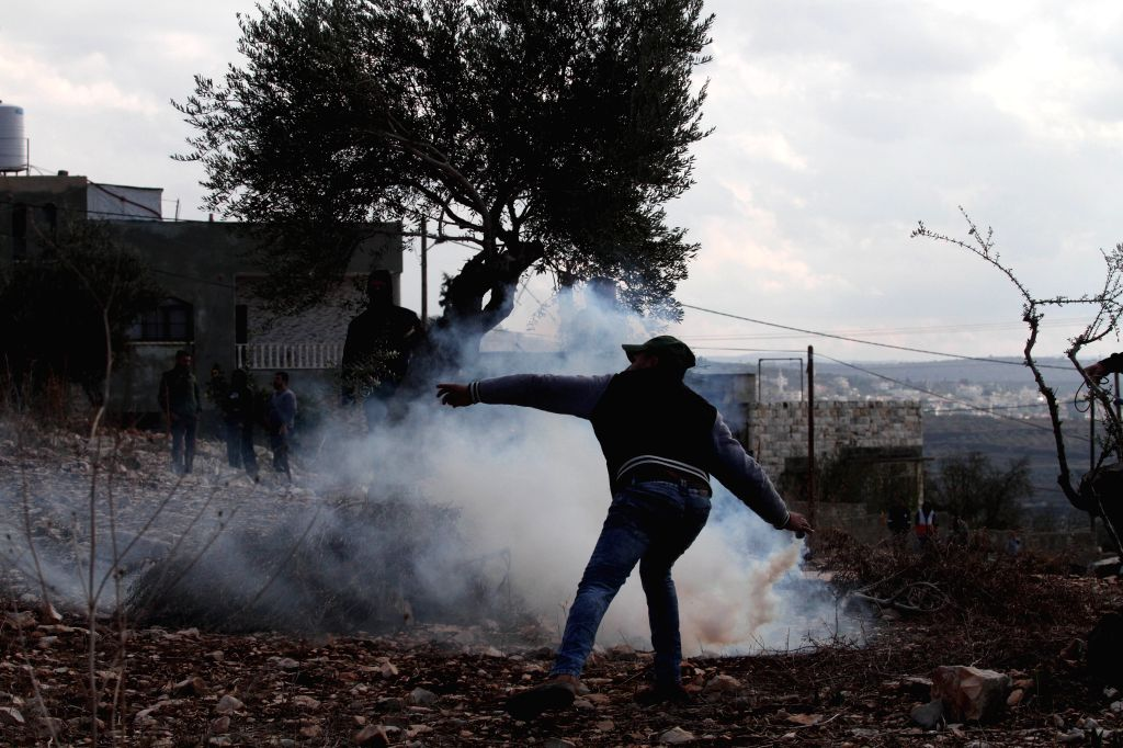 NABLUS, Dec. 6, 2019 - A Palestinian man throws back a tear gas canister fired by Israeli soldiers during clashes after a protest against the expanding of Jewish settlements in Kufr Qadoom village ...