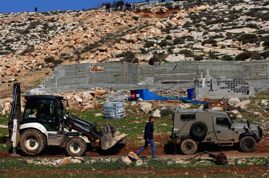 NABLUS, Feb. 1, 2018 - An Israeli bulldozer is seen near a house under construction in Beit Dajan village near the West Bank city of Nablus, on Feb. 1, 2018. The Israeli army demolished a Palestinian ...