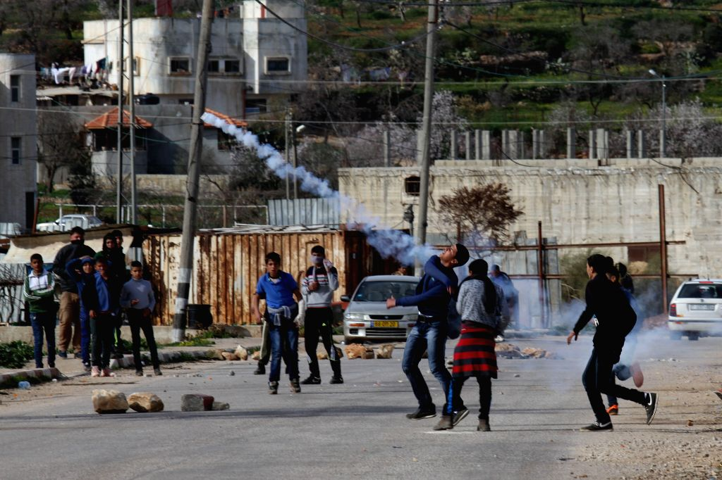 A Palestinian protester hurls back a tear-gas canister shot by Israeli soldiers during clashes near the Jewish settlement of Majdolim, close to Qusra village, south ..