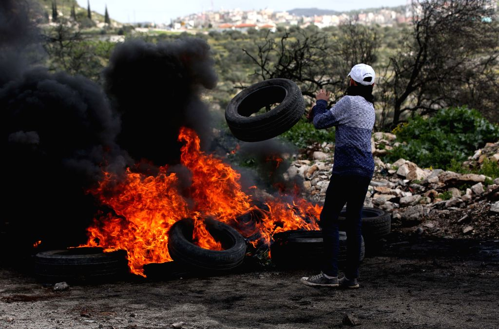 NABLUS, Feb. 8, 2019 - A Palestinian protester burns tires during clashes with Israeli soldiers, after a protest against the expanding of Jewish settlements in Kufr Qadoom village near the West Bank ...