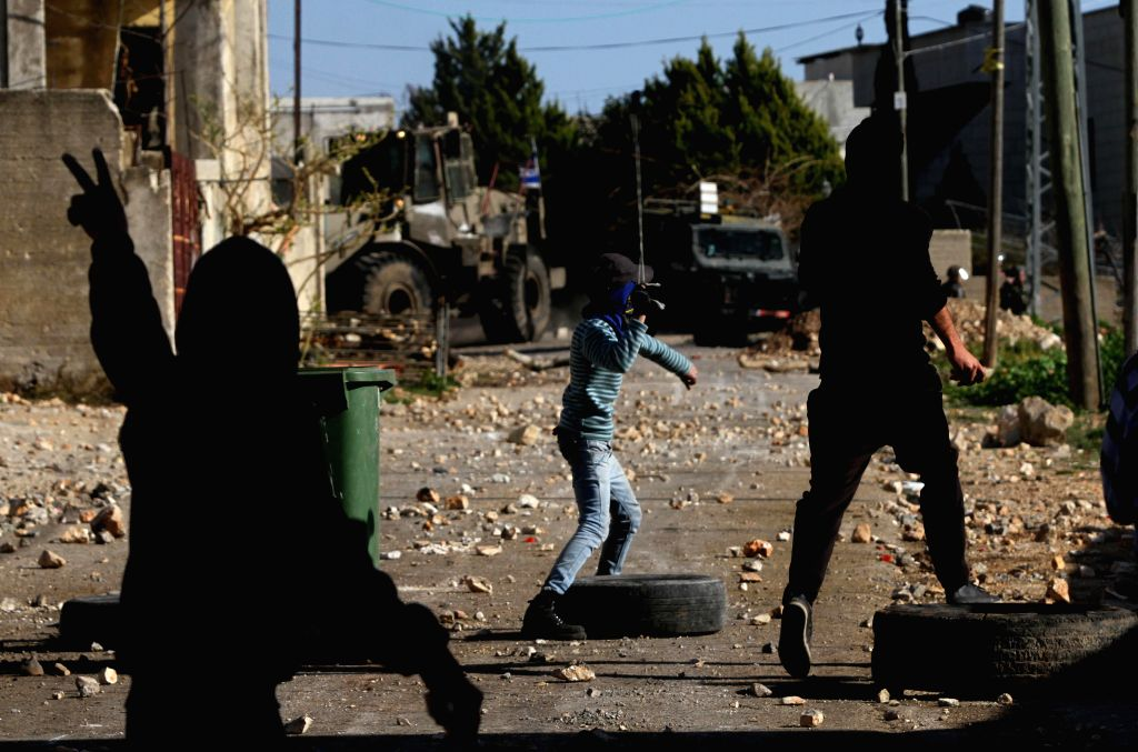 A Palestinian protester throws stones at Israeli soldiers during a protest against the expanding of Jewish settlements in Kufr Qadoom village near the West Bank city