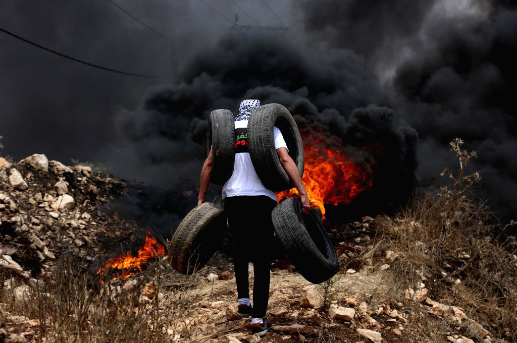 NABLUS, July 13, 2018 - A Palestinian protester holds tires to burn them during clashes with Israeli soldiers after a protest against the expanding of Jewish settlements in Kufr Qadoom village near ...