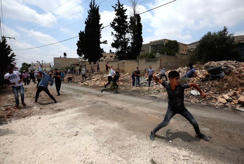 NABLUS, July 13, 2018 - Palestinian protesters hurl stones at Israeli soldiers during clashes with Israeli soldiers after a protest against the expanding of Jewish settlements in Kufr Qadoom village ...