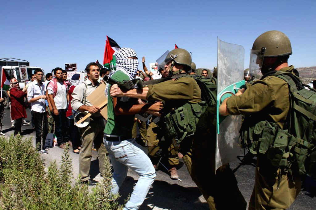 Palestinian protesters clash with Israeli soldiers during a protest against the ongoing Israeli air campaign against Gaza at the Howwara checkpoint near the West ...