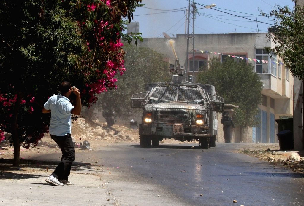 NABLUS, July 22, 2016 - A Palestinian protester hurls a stone at Israeli force during clashes after a protest against the expanding of Jewish settlements in Kufr Qadoom village near the West Bank ...