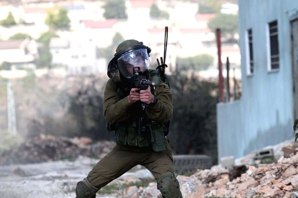 NABLUS, July 28, 2018 - An Israeli soldier aims his weapon at Palestinian protesters during clashes after a protest against the expanding of Jewish settlements in Kufr Qadoom village near the West ...
