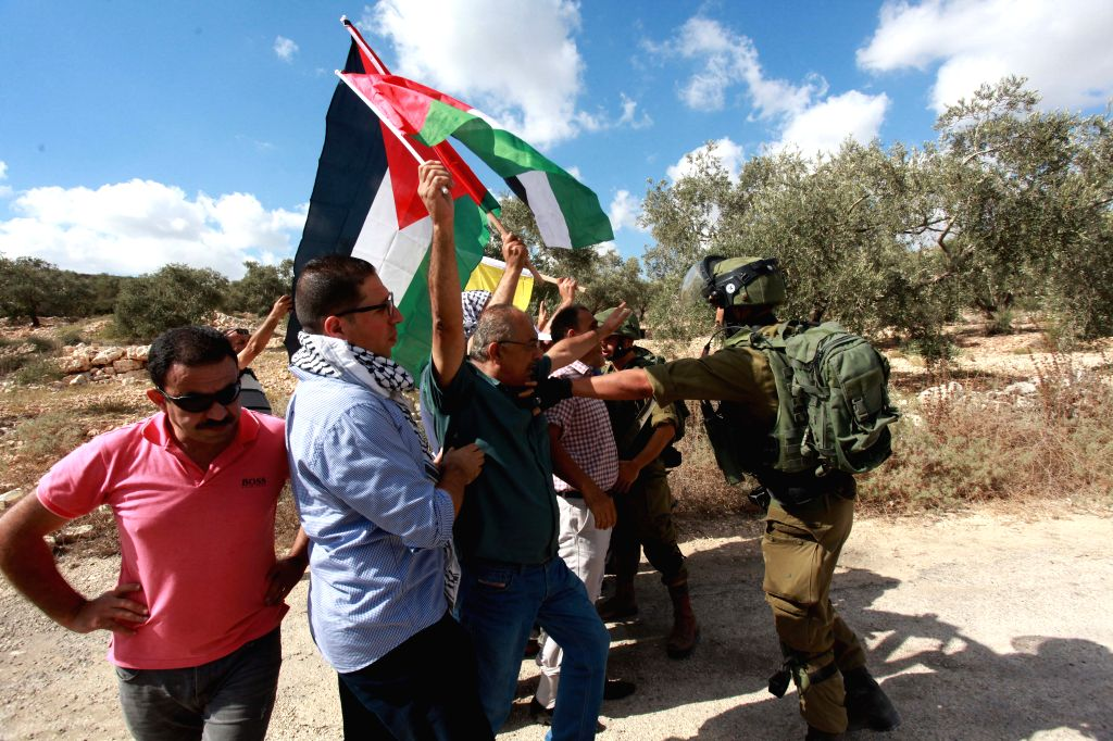 NABLUS, July 28, 2018 - An Israeli soldier pushes back Palestinian protesters during a protest against the expanding of Jewish settlements in Kufr Qadoom village near the West Bank city of Nablus, on ...
