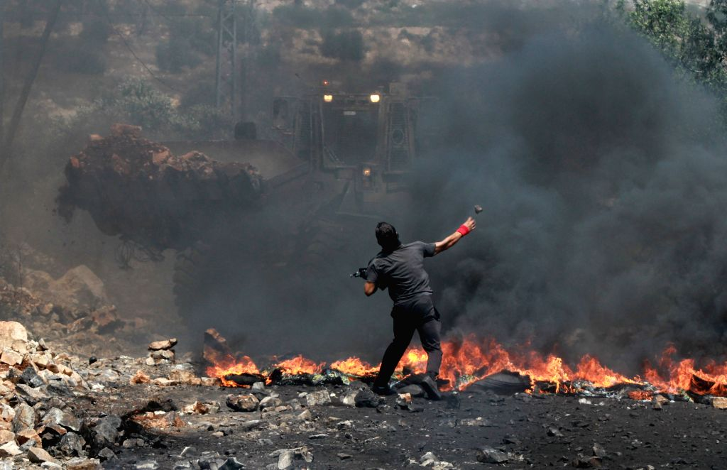 A Palestinian protester throws stones at Israeli soldiers during a protest against the expanding of Jewish settlements in Kufr Qadoom village near the West Bank city .