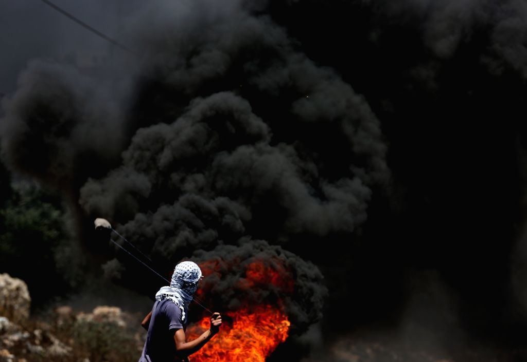 NABLUS, June 30, 2017 - A Palestinian protester uses slingshot to hurl stones at Israeli soldiers during clashes after a protest against the expanding of Jewish settlements in Kufr Qadoom village ...