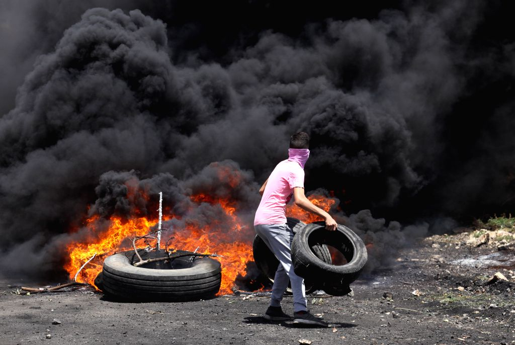 NABLUS, June 7, 2019 - A Palestinian protester burns tires during clashes with Israeli soldiers after a protest against the expansion of Jewish settlements in Kufr Qadoom village near the West Bank ...