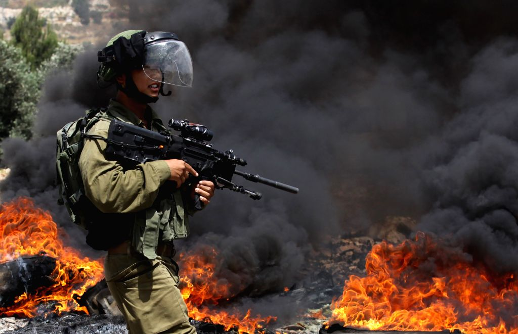NABLUS, June 7, 2019 - An Israeli soldier holds his weapon during clashes with Palestinian protesters after a protest against the expansion of Jewish settlements in Kufr Qadoom village near the West ...