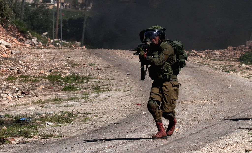 NABLUS, March 9, 2019 - An Israeli soldier aims his weapon at Palestinian protesters during clashes, after a protest against the expanding of Jewish settlements in Kufr Qadoom village near the West ...