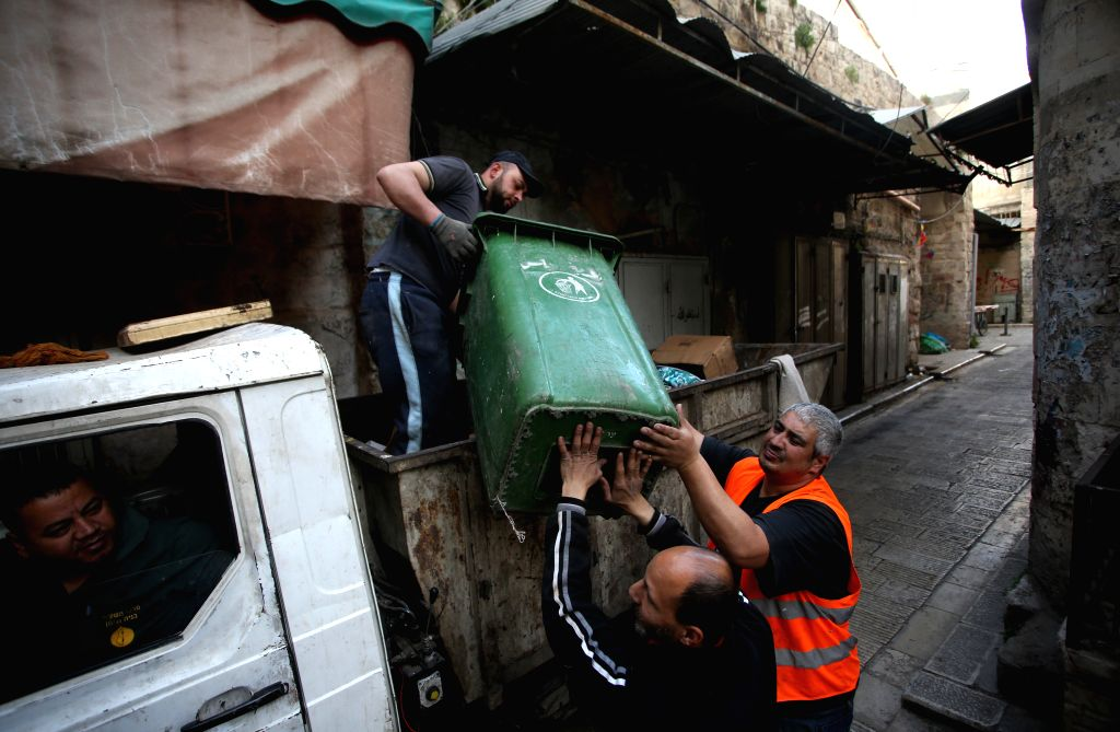 NABLUS, May 1, 2019 - Palestinian workers lift a trash bin on the International Labor Day in the West Bank city of Nablus, on May 1, 2019.