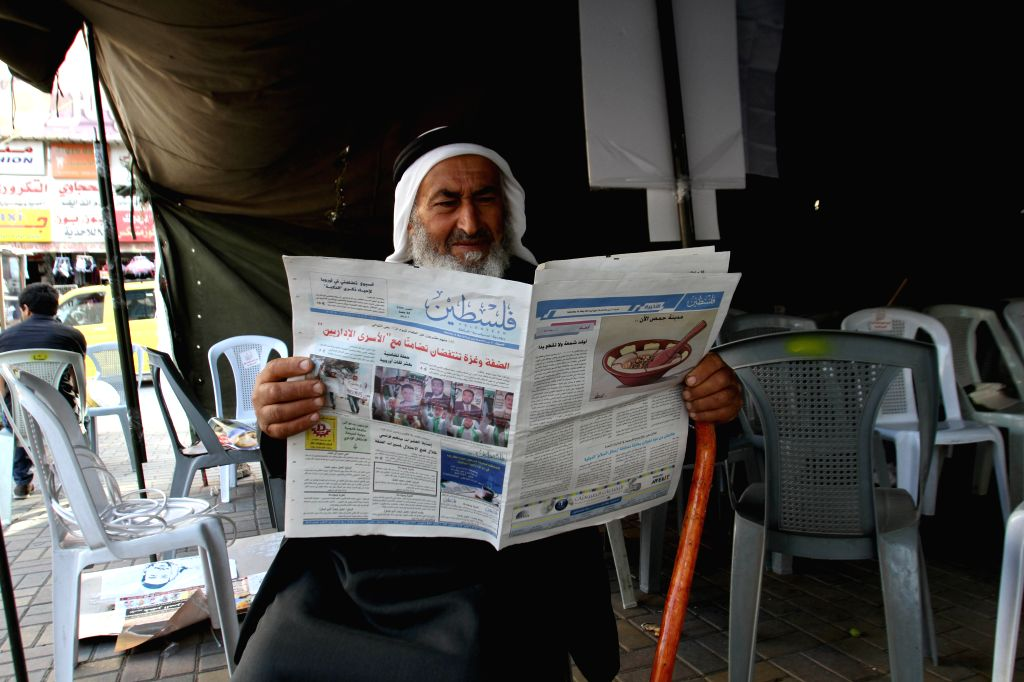 """A Palestinian reads a copy of the """"PALESTINA"""" newspaper in the West Bank City of Nablus, on May 10, 2014. Palestinian government allowed the redistribution ."""