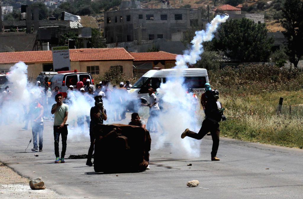 NABLUS, May 12, 2017 - A Palestinian protester throws back a tear gas canister at Israeli soldiers during clashes in the West Bank village of Beit Furik, east of Nablus, on May 12, 2017, after a ...