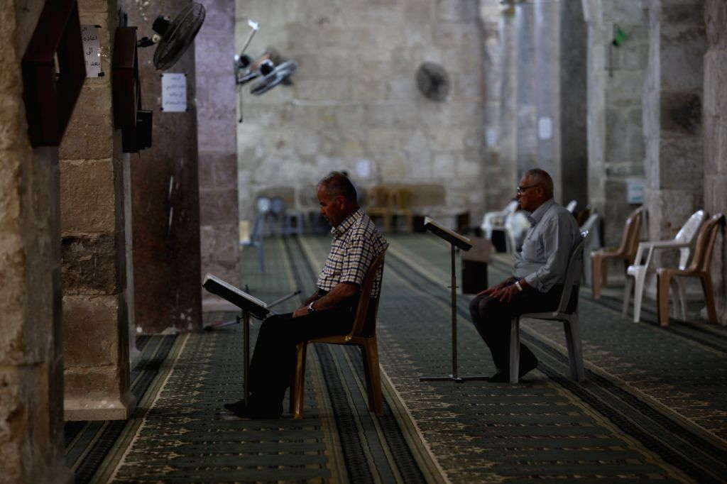 NABLUS, May 12, 2019 - Palestinian men read Quran inside a mosque during the Muslim fasting month of Ramadan in the West Bank city of Nablus, May 12, 2019.