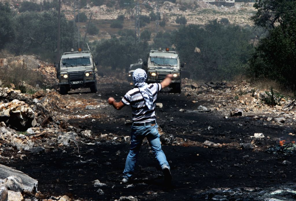 A Palestinian protester throws stones at Israeli soldiers during a protest against the expanding of Jewish settlements in the Kufr Qadoom village near the West Bank ..