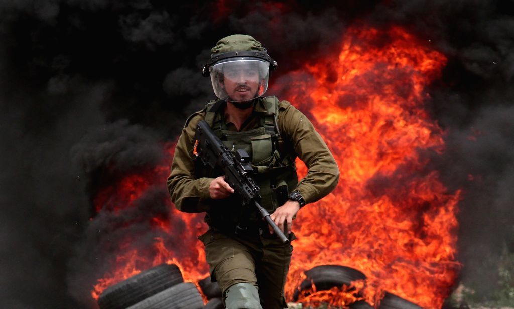NABLUS, May 24, 2019 - An Israeli soldier holds his weapon during clashes with Palestinian protesters after a protest against the expanding of Jewish settlements in Kufr Qadoom village near the West ...