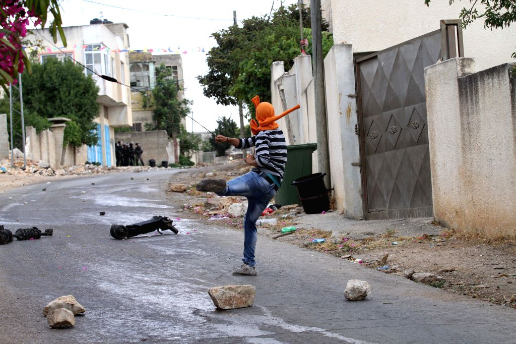 NABLUS, May 27, 2016 - A Palestinian protester hurls stones at Israeli soldiers during clashes following a demonstration against the expanding of Jewish settlements in Kufr Qadoom village near the ...