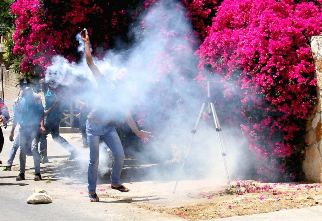 NABLUS, May 27, 2016 - A Palestinian protester hurls a tear gas canister back towards Israeli soldiers during clashes following a demonstration against the expanding of Jewish settlements in Kufr ...