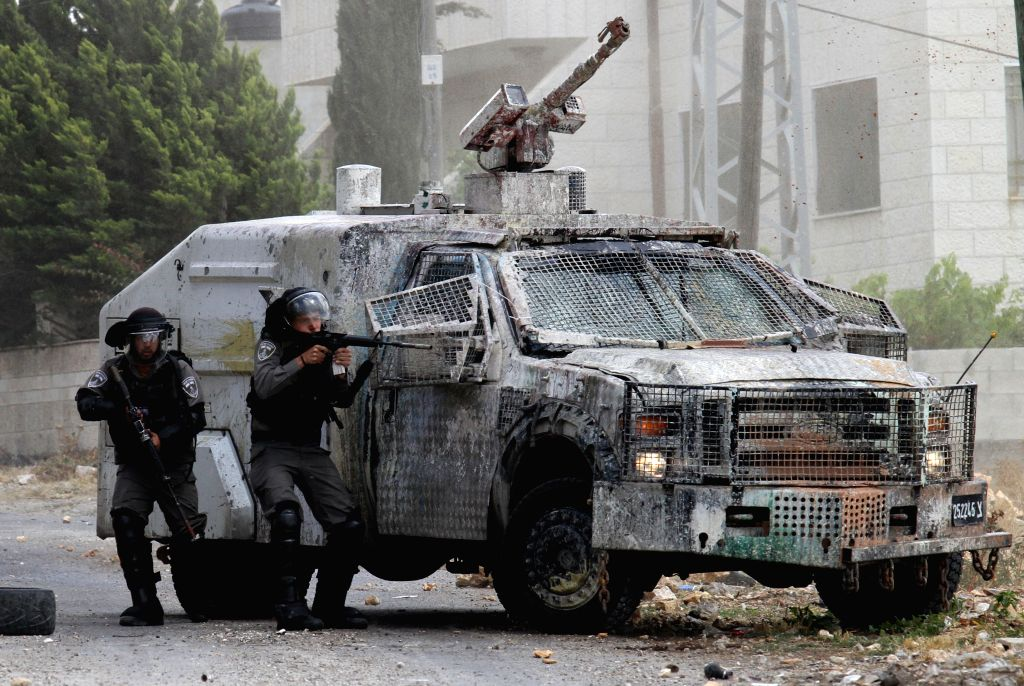 NABLUS, May 27, 2016 - Israeli soldiers stand guard next to their armored vehicle during clashes with protesters following a demonstration against the expanding of Jewish settlements in Kufr Qadoom ...