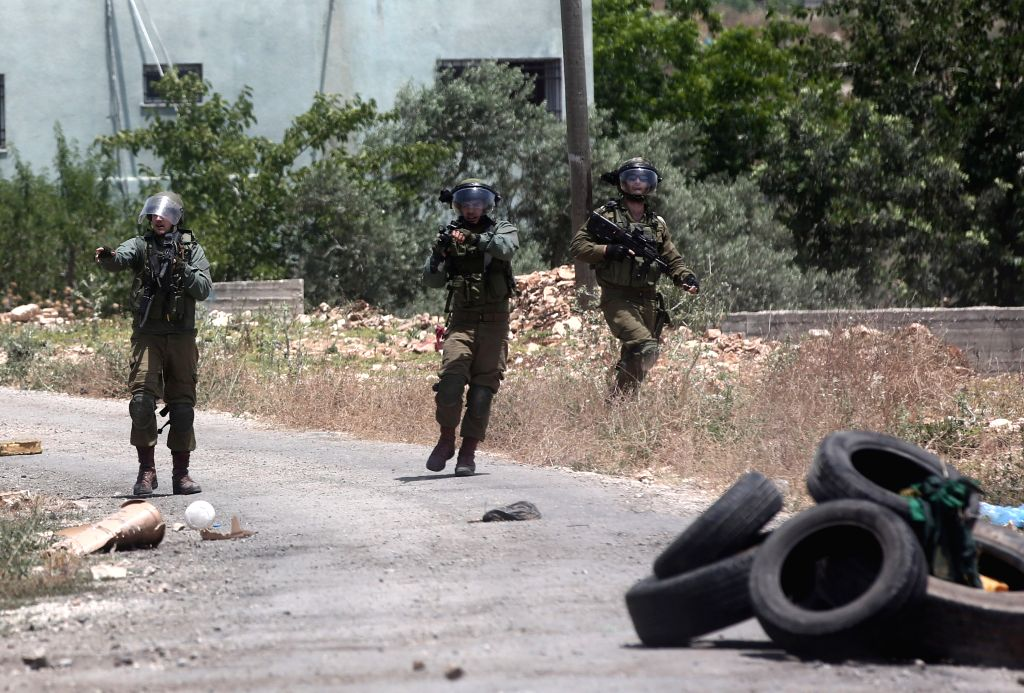 NABLUS, May 31, 2019 - Israeli soldiers react during clashes with Palestinian protesters after a protest against the expanding of Jewish settlements in Kufr Qadoom village near the West Bank city of ...
