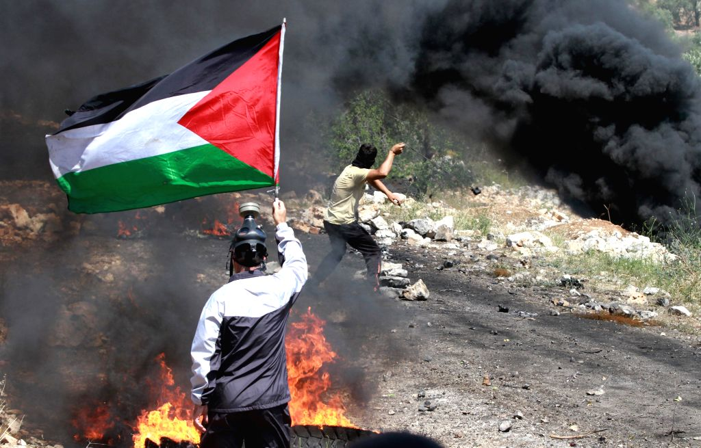 A Palestinian protester holds a flag as he takes part in a protest against the expanding of Jewish settlements in Kufr Qaddoum village near the West Bank city of ...