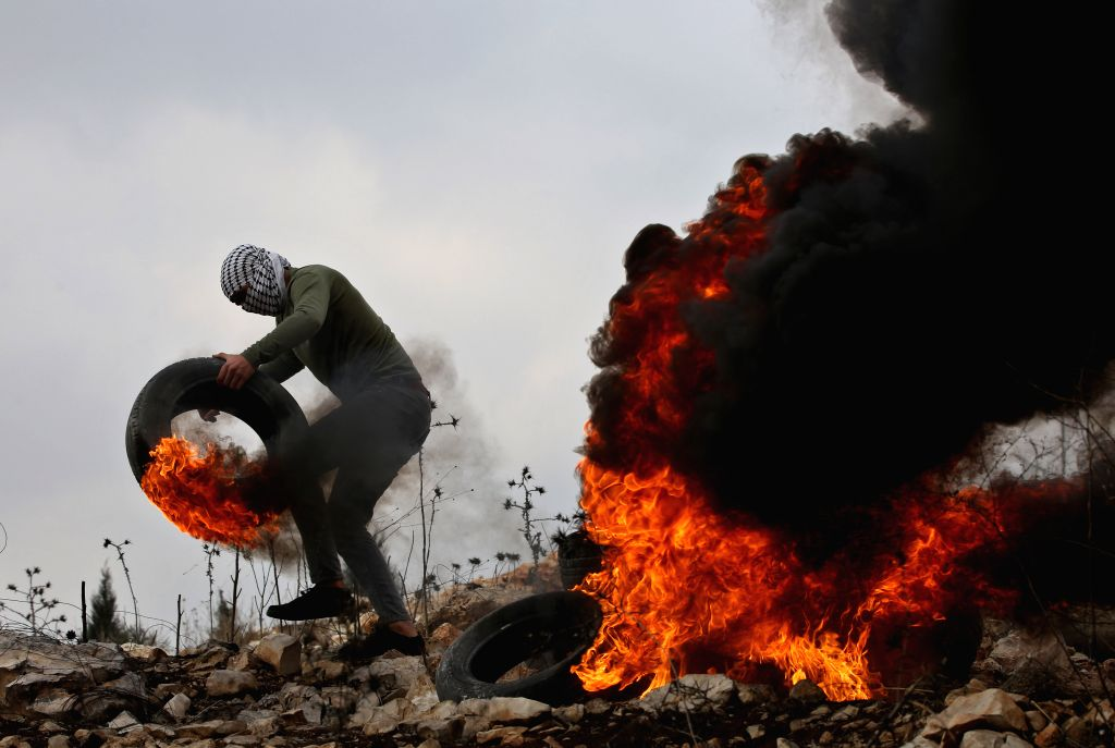 NABLUS, Nov. 15, 2019 - A Palestinian protester burns tires during clashes with Israeli soldiers during clashes, after a protest against the expanding of Jewish settlements in Kufr Qadoom village ...