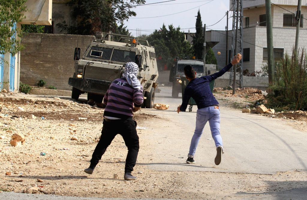 NABLUS, Oct. 13, 2017 - A Palestinian protester hurls stones at Israeli soldiers during clashes after a protest against the expanding of Jewish settlements in Kufr Qadoom village near the West Bank ...