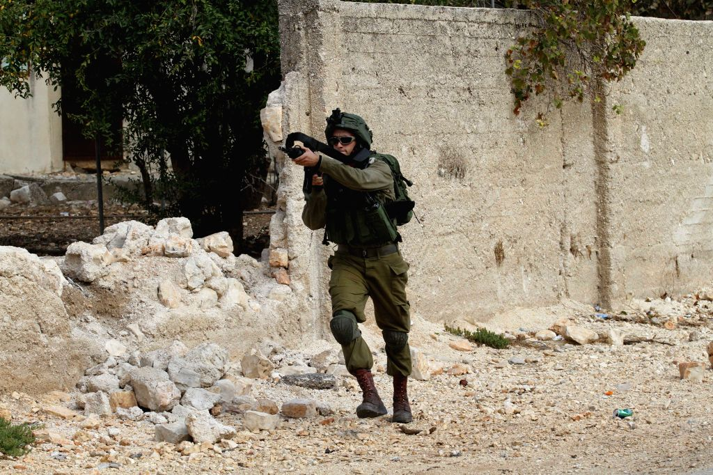 NABLUS, Oct. 13, 2017 - An Israeli soldier aims his weapon at Palestinian protesters during clashes after a protest against the expanding of Jewish settlements in Kufr Qadoom village near the West ...