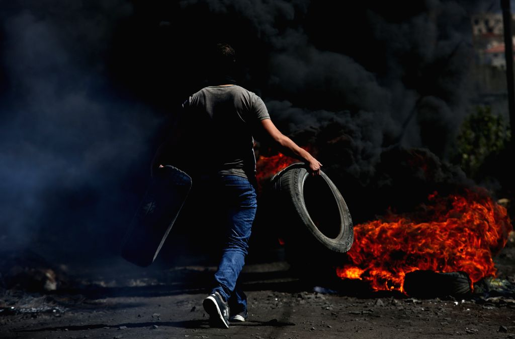 NABLUS, Oct. 7, 2016 - A Palestinian protester burns tires during clashes with Israeli soldiers after a protest against the expanding of Jewish settlements in Kufr Qadoom village near the West Bank ...