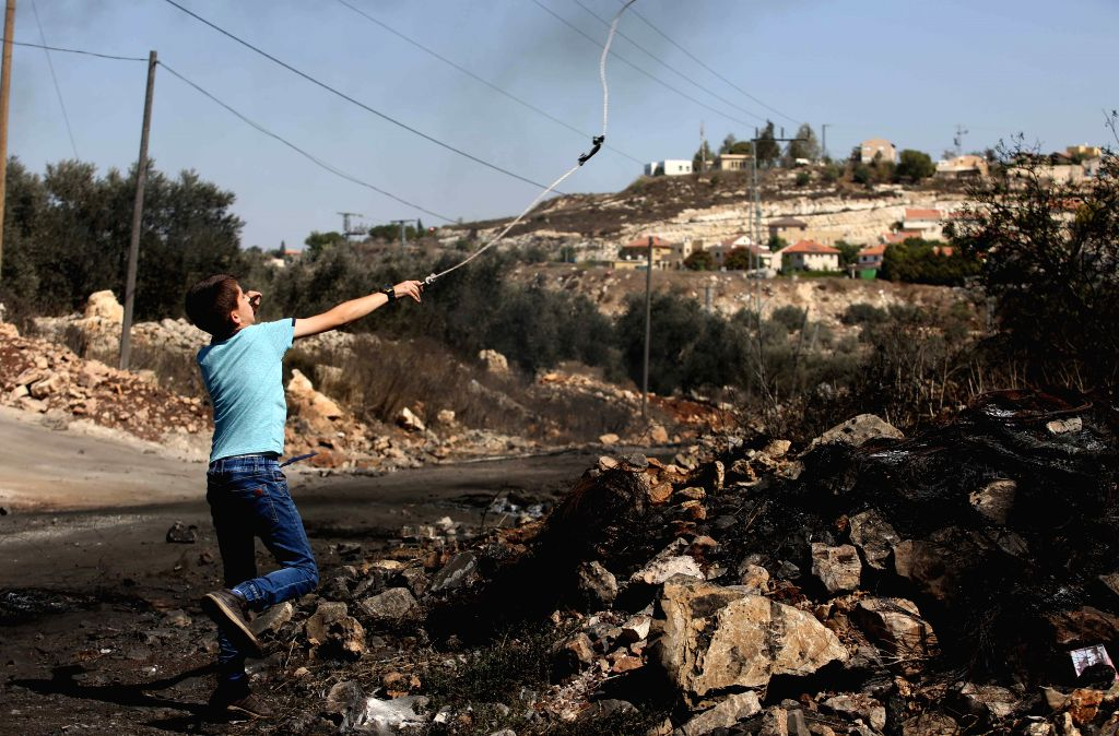 NABLUS, Oct. 7, 2016 - A Palestinian protester hurls stones at Israeli soldiers during clashes after a protest against the expanding of Jewish settlements in Kufr Qadoom village near the West Bank ...