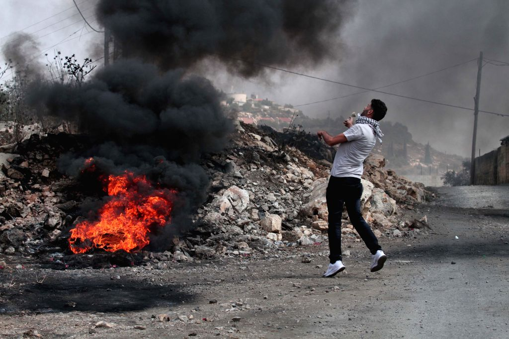NABLUS, Sept. 13, 2019 - A Palestinian hurls stones at Israeli soldiers during clashes, after a protest against the expanding of Jewish settlements in Kufr Qadoom village, near the West Bank city of ...