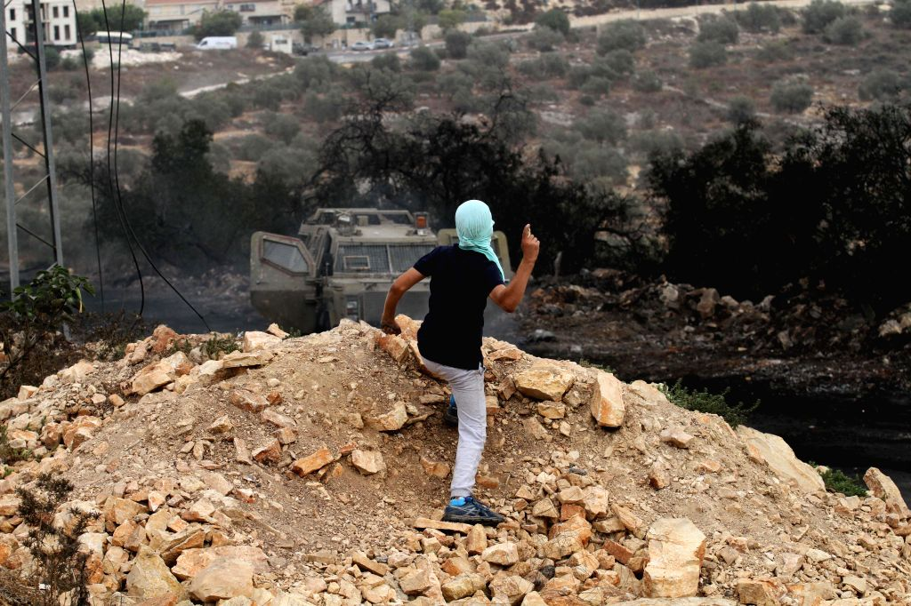 NABLUS, Sept. 15, 2017 - A Palestinian protester hurls stones at Israeli soldiers during clashes after a protest against the expanding of Jewish settlements in Kufr Qadoom village near the West Bank ...