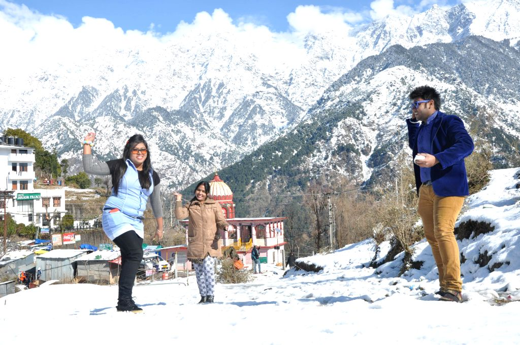 Tourists enjoy themselves in snow clad Naddi near Dharamsala, Himachal Pradesh on Jan 15, 2015.